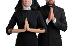 Nun and priest praying isolated on a white background. Royalty Free Stock Photo
