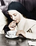 Nun sipping tea out of a teacup with a straw Royalty Free Stock Image