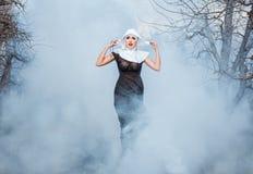 Nun in the smoke. Royalty Free Stock Photos