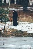 Nun stands next pond. STAROSILLIA, Volyn / UKRAINE - February 04 2009: Nun stands at a pond in woods in winter Royalty Free Stock Photography