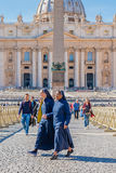 Nun walk through Saint Peter`s square by the Basilica in Vatican Stock Photo