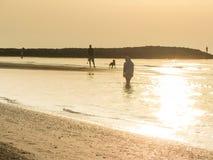 A nun walking long the shoreline of an Italian beach in the earl Stock Photo