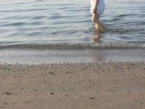 A nun walking long the shoreline of an Italian beach in the early morning Stock Image
