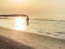 A nun walking long the shoreline of an Italian beach in the early morning Royalty Free Stock Photo