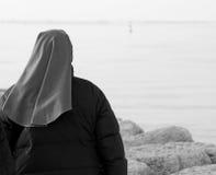 Nun walks in winter near the ocean Royalty Free Stock Photo