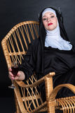 Nun with wine in headphones. Nun with bright makeup sitting on a chair, drinking wine and listening to music on headphones Stock Images