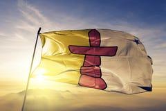 Nunavut landskap av tyg för torkduk för Kanada flaggatextil som vinkar på den bästa soluppgångmistdimman royaltyfri foto