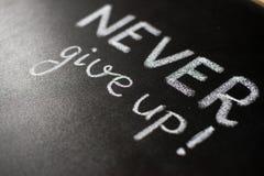 Nunca abandone, negocio o enseñe las palabras de motivación Fotografía de archivo