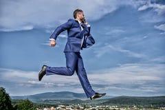 Nunca pare Salto formal del traje del hombre de negocios mientras que fondo del cielo del smartphone de la llamada Empresario en  imágenes de archivo libres de regalías