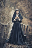Nun stand on the wooden bridge with black cloak,cross,X. Stock Photos