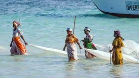 Nungwi, Zanzibar, Tanzania Afryka Wschodnia, Czerwiec, - 23, 2017: Afrykańskie kobiety od wioski rybackiej łapać małej ryba zarab Fotografia Stock