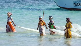 Nungwi, Zanzibar, Tanzania, East Africa - June 23, 2017: African women from a fishing village to catch small fish nets in the ocea. N stock photography