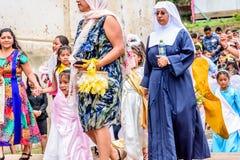 Nunna & änglar i den katolska processionen, San Juan del Obispo, Guatem Arkivfoton