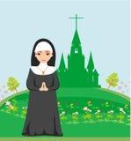 Nunna som framme ber av kyrkan Arkivfoton