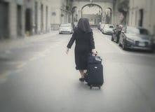 Nunna som håller bagage på vägen royaltyfria bilder