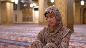 Nunnan i ämbetsdräkt sitter på en matta inom en islamisk moské egypt stock video