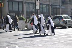 Nunnor som korsar gatan i New York City arkivfoto