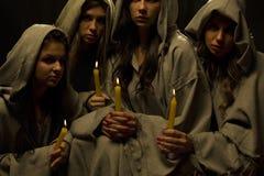 Nunnor som praing med stearinljus Arkivfoto