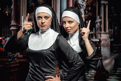 Nuns. Attractive young nuns posing in the church stock photo