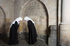 Nuns greeting. Two nuns greeting eachother inside a medieval abbey royalty free stock photography