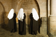 Nuns in medieval convent. Young nuns facing the walls of a 14th century medieval abbey royalty free stock photo