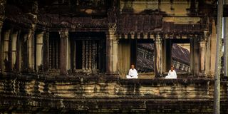 Nuns meditate on the ruin of Angkor Wat at sunrise Royalty Free Stock Image