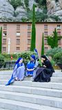 Nuns and novices on the steps of the temple talk and laugh; a trip to the Montserrat mountain; royalty free stock image