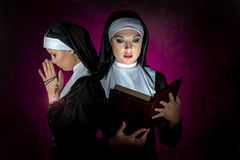 Nuns. Two attractive young nuns with rosary and bible praying stock photo