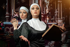 Nuns. Two attractive young nuns with rosary and bible praying in the church royalty free stock image