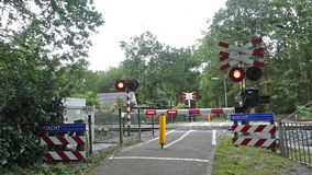 Dutch intercity double decker electric train riding through train crossing with barriers to block traffic, bikes and pedestrians stock video