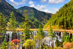 The Nuo Ri Lang Waterfall Nuorilang among wooded mountains. Amazing view of the Nuo Ri Lang Waterfall Nuorilang among wooded mountains and colorful fall forest Stock Photo