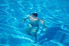Nuotata dell'uomo sotto acqua blu Immagini Stock