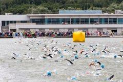 Nuotata di Triathletes sull'inizio della concorrenza di triathlon nel fiume di Mosca e degli spettatori dietro la scena Fotografia Stock