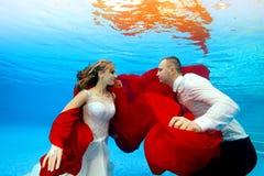 Nuotata felice dello sposo e della sposa subacquea al tramonto Si esaminano reciprocamente ed il sorriso con un panno rosso in lo fotografia stock libera da diritti