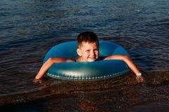 Nuotate allegre del bambino nel mare con un cerchio di gomma blu fotografie stock