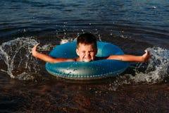 Nuotate allegre del bambino nel mare con un cerchio di gomma blu fotografia stock