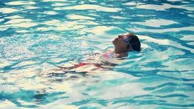 Nuotate della ragazza nello stagno sulla parte posteriore, in vetri speciali per lo stagno, vetri di nuoto video d archivio