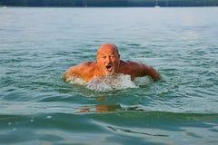 Nuotatore, colpi di farfalla di nuoto dell'uomo senior Maschio caucasico di 60 anni Fotografia Stock
