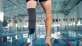 Nuotatore con un addestramento della protesi della gamba vicino ad uno stagno, attrezzatura bionica archivi video