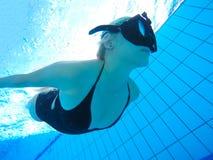 Nuotatore femminile che zampilla attraverso l'acqua in stagno immagine stock