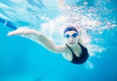 Nuotatore femminile che zampilla attraverso l'acqua in stagno Fotografia Stock