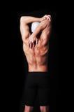 Nuotatore maschio muscolare che posa e che fa allungamento Immagine Stock