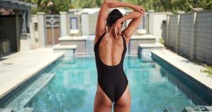 Nuotatore millenario della donna della corsa mista che allunga prima del salto nello stagno Immagine Stock Libera da Diritti
