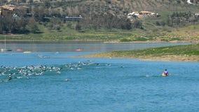 Nuotatori che nuotano nel triathlon di sport in un lago video d archivio