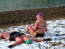 Nuotatori sulla spiaggia nella neve Immagini Stock