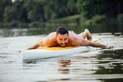 Nuoto atletico dell'uomo su un paddleboard Immagini Stock Libere da Diritti