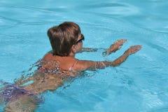Nuoto caucasico della donna nello stagno all'aperto Fotografia Stock