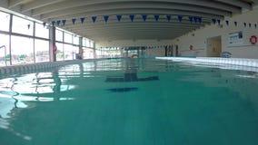 Nuoto caucasico di mezza età dell'uomo nell'acqua, nella piscina in Palamos in Spagna video d archivio