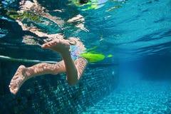 Nuoto del bambino con il divertimento sull'anello giallo in stagno blu Fotografia Stock Libera da Diritti