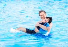 Nuoto del padre nello stagno con il bambino disabile Fotografie Stock